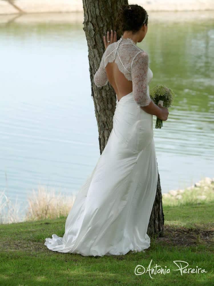 Novia de espaldas con tocado de novia y precioso ramo de flores