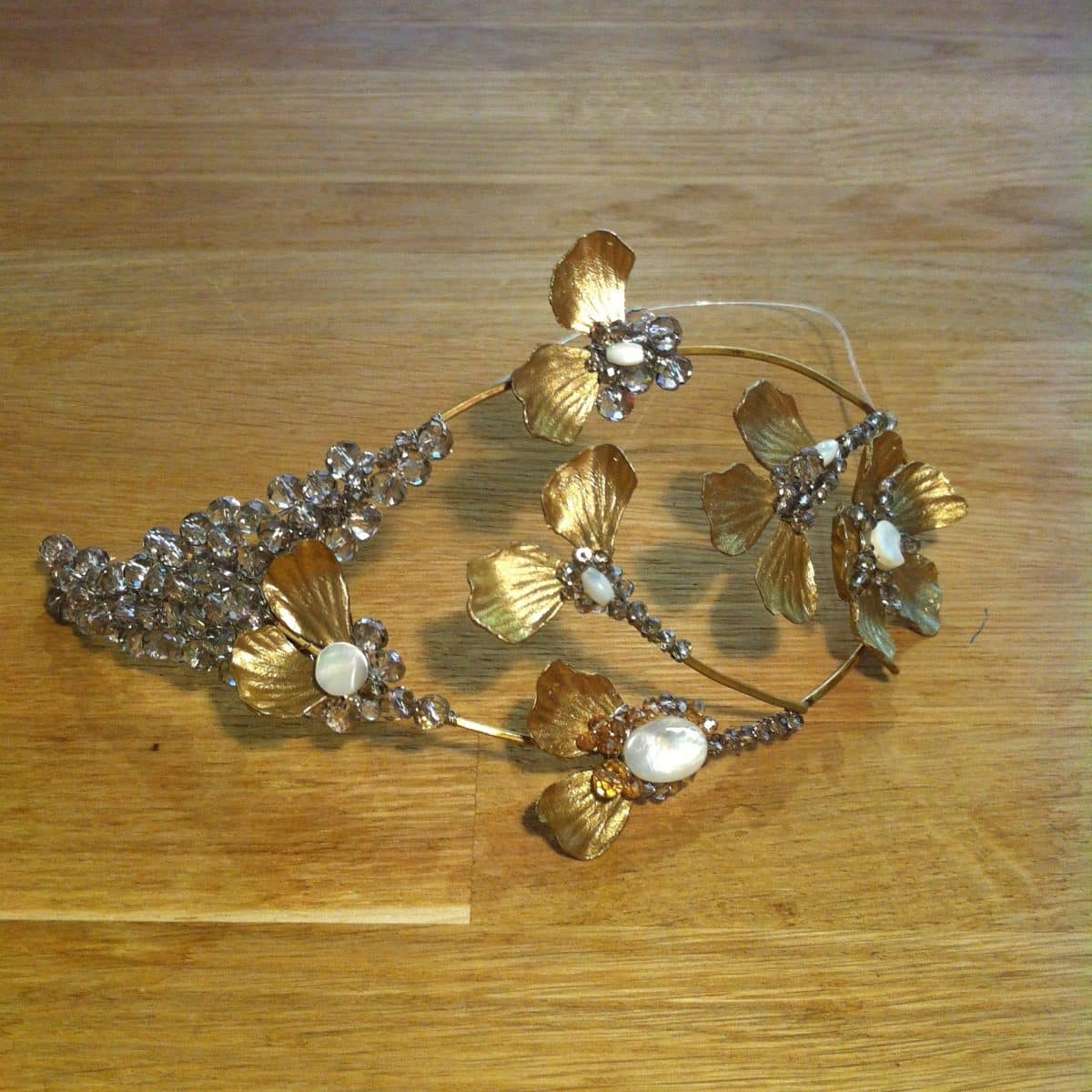Tocado de novia en metal y cristal sobre mesa de madera