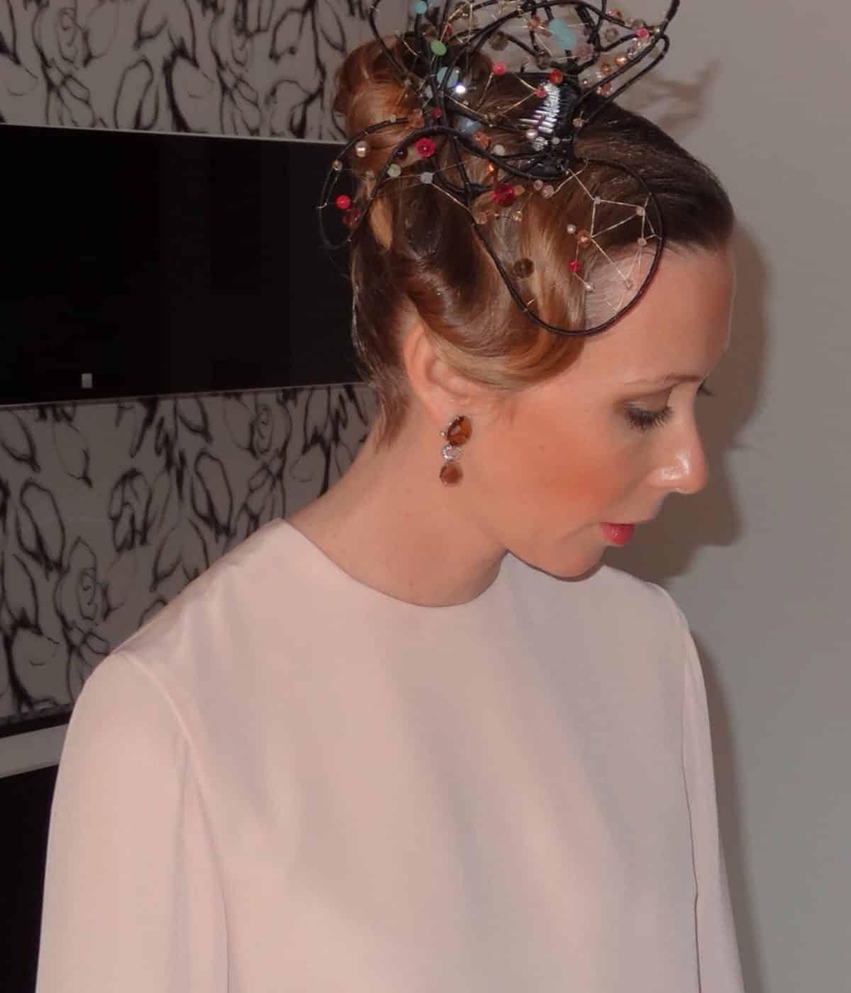 Hermana de la novia con peinado recogido, tocado de fantasia y vestido color maquillaje