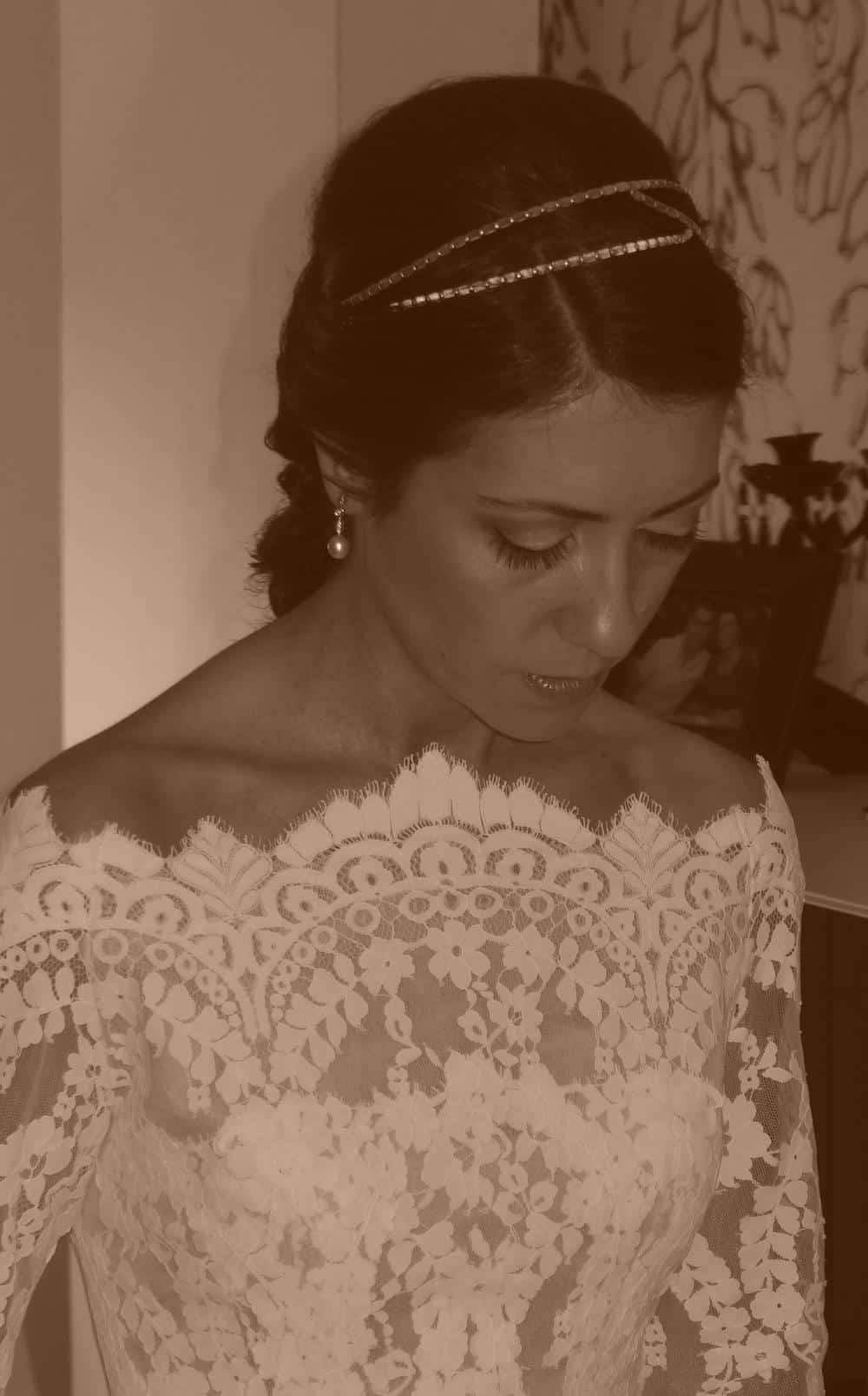Tocado de boda para novia con diadema dorada y vestido de encaje blanco