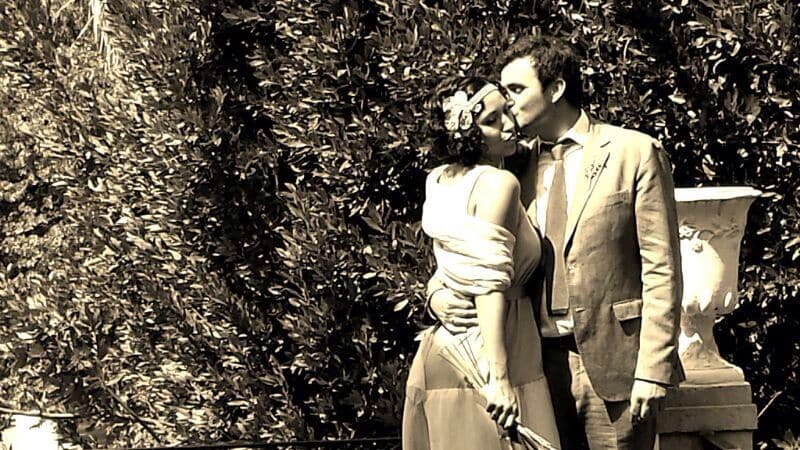 Beso de dos novios posando en un jardín. Destaca tocado joya de la novia.