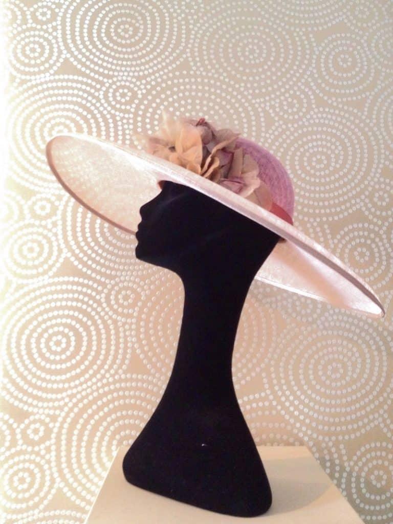 Pamela con ala en color hueso, adorno y copa rosa sobre cabeza de exibición. Sombreros y Pamelas Monic