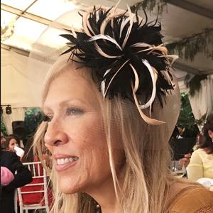 invitada de boda con tocado de plumas negras